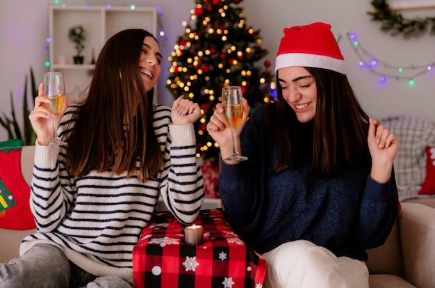 Ridendo belle ragazze tenere bicchieri di champagne seduti su poltrone e godersi il periodo natalizio a casa