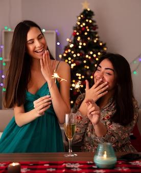 笑っているかわいい若い女の子は線香花火を持って、テーブルに座って家でクリスマスの時間を楽しんでいる口の近くに手を保ちます