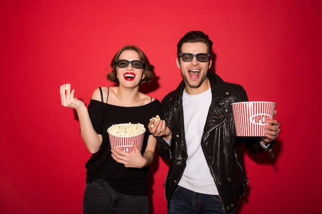 Laughing punk couple eating popcorn and looking
