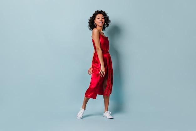 Смеющаяся красная женщина в белых кедах, глядя на фронт
