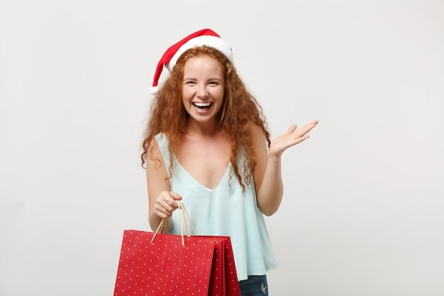 白い背景で隔離のクリスマス帽子で赤毛のサンタの女の子を笑う。明けましておめでとうございます2020年のお祝いの休日のコンセプト。コピースペースをモックアップします。買い物の後にギフトや購入品が入ったパッケージバッグを持ってください。