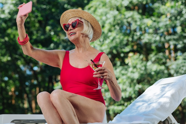 Laughing retired woman wearing bright red sunglasses making photos while sunbathing