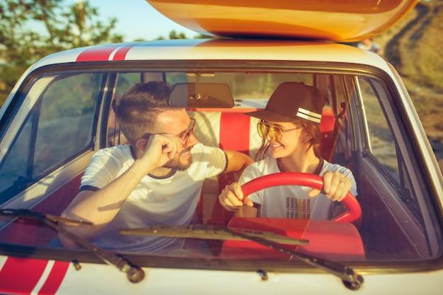 Ridendo coppia romantica seduti in macchina durante un viaggio su strada. coppie che hanno picnic al giorno d'estate