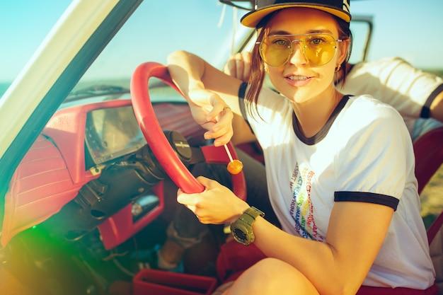 Ridendo coppia romantica seduti in macchina durante un viaggio in una giornata estiva