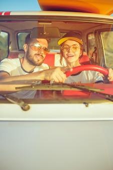 도로 여행을하는 동안 차에 앉아 로맨틱 커플을 웃고