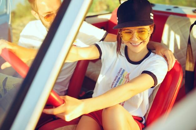 ロードトリップ中に車の中で座って笑うロマンチックなカップル。夏の日にピクニックをしているカップル