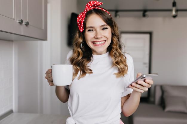 Смеющаяся романтическая девушка с красной лентой, наслаждаясь утром с кофе. крытый снимок симпатичной кудрявой дамы, держащей чашку чая и телефон.