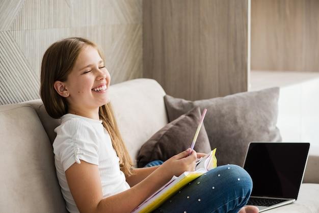 笑っている女子高生は、鉛筆、教科書、ノートを持って自宅のソファに座っています