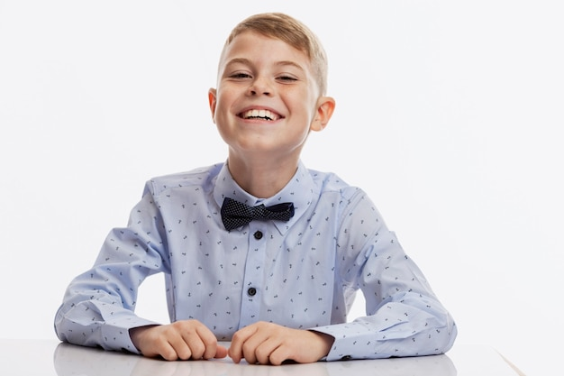 Laughing schoolboy in a blue shirt with a bow tie sits at the table. back to school. white background.