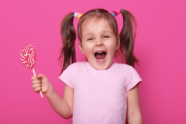 Laughing screaming cute girl opens her mouth widely, showing teeth, holds in one hand heart bright tasty lollipop. emotional positive childen spends her leisure time with pleasure. copy space for ad.