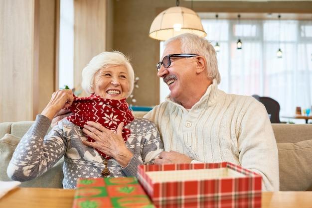 Смеется пожилая пара, наслаждаясь рождеством