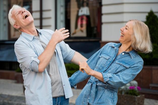街でアウトドアを楽しむシニアカップルを笑ってください。