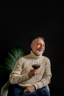 Laughing senior man with glass of wine