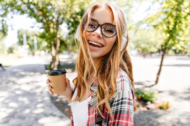 公園でお茶を楽しんで笑う壮大な女性。自然の中でコーヒーを飲むスタイリッシュな白人の女の子。
