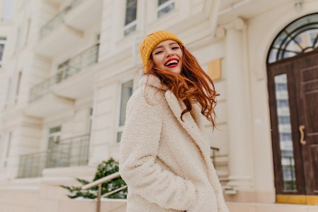 추운 날에 포즈를 취하는 화려한 여자를 웃고 있습니다. 겨울을 즐기는 밝은 화장으로 매력적인 여자의 야외 초상화.