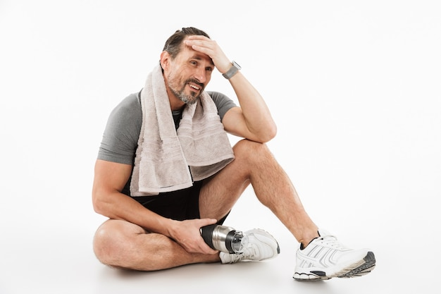 Laughing strong mature sportsman sitting with towel and water