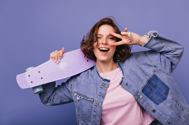 Laughing stylish woman in oversize jacket holding skateboard. indoor photo of glad female model isolated.