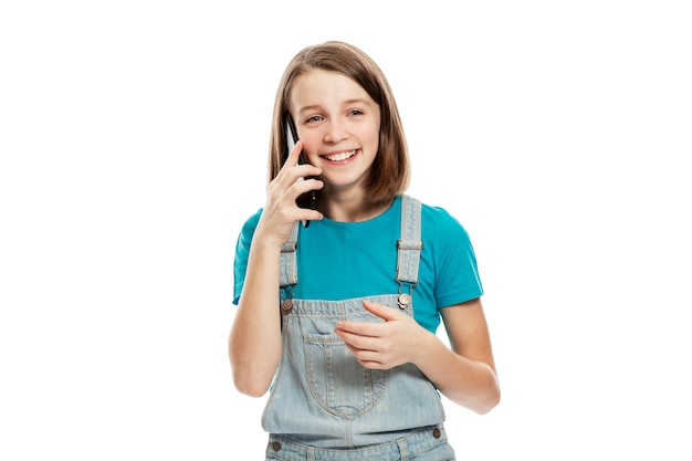 Laughing teenage girl in denim overalls and a blue t-shirt talking on a smartphone. .
