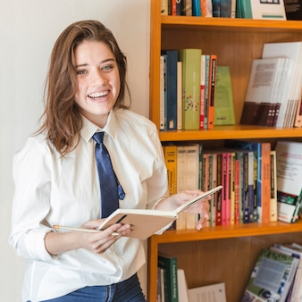 Laughing teenager with notebook near bookcase