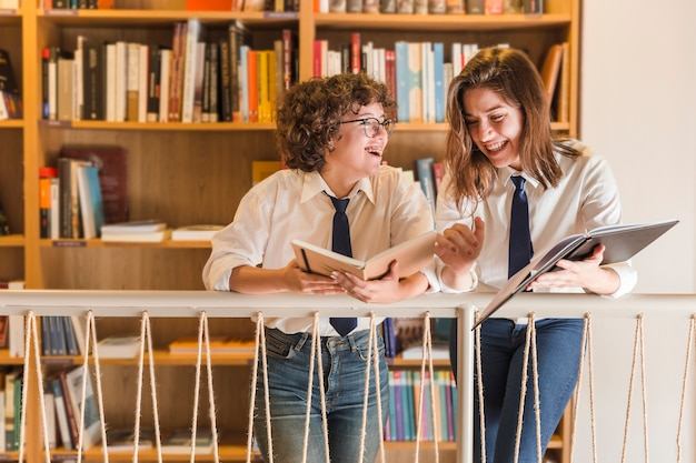 Laughing teenagers with books chatting in library