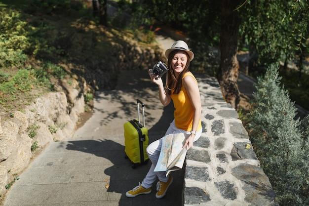 屋外でレトロなビンテージ写真カメラを保持しているスーツケースの都市地図とカジュアルな服の帽子で旅行者の観光客の女性を笑っています。週末の休暇に旅行するために海外に旅行している女の子。観光の旅のライフスタイル。