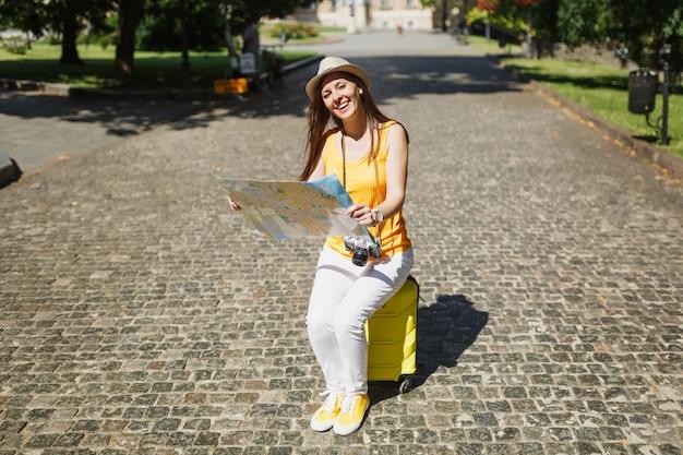 노란색 옷 모자를 쓴 여행자 관광 여성이 도시 야외에서 도시 지도 검색 경로를 들고 여행가방에 앉아 웃고 있습니다. 주말 휴가를 여행하기 위해 해외로 여행하는 소녀. 관광 여행 라이프 스타일.