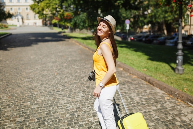 Laughing traveler tourist woman with closed eyes in yellow summer casual clothes hat with suitcase walk in city outdoor. girl traveling abroad to travel on weekends getaway. tourism journey lifestyle.