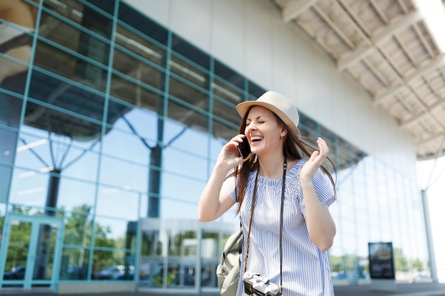 Laughing traveler tourist woman with retro vintage photo camera talk on mobile phone calling friend,