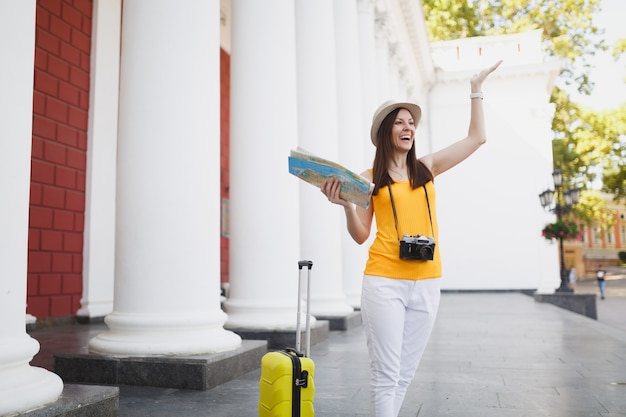 Laughing traveler tourist woman with suitcase, city map retro vintage photo camera meeting friend, spreading hands in city outdoor. girl traveling abroad on weekend getaway. tourism journey lifestyle.