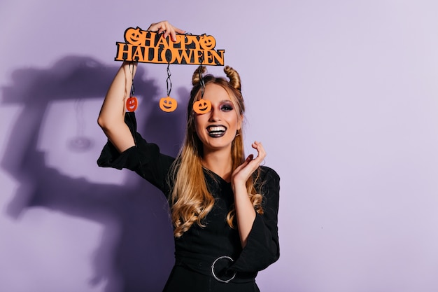 Laughing white girl in halloween dress posing on purple wall. lovely female model in party attire expressing positive emotions.