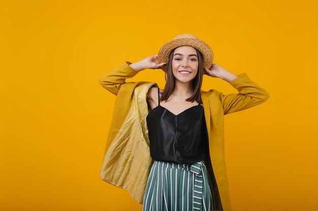麦わら帽子のポーズで魅力的な女性を笑う。孤立した黒いタンクトップの魅力的な女性。
