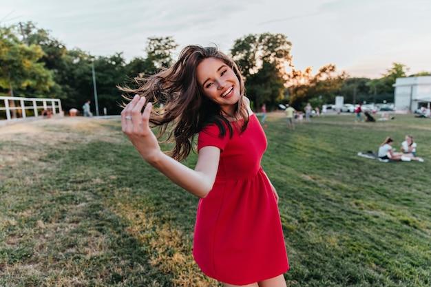 검은 머리 포즈와 함께 winsome 여자를 웃고. 공원에서 춤추는 빨간 드레스에 평온한 여성 모델.