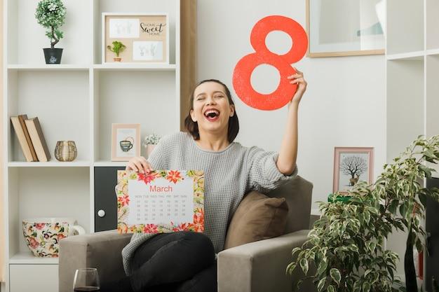 Смеясь с закрытыми глазами, красивая девушка в счастливый женский день держит номер восемь с календарем, сидя на кресле в гостиной