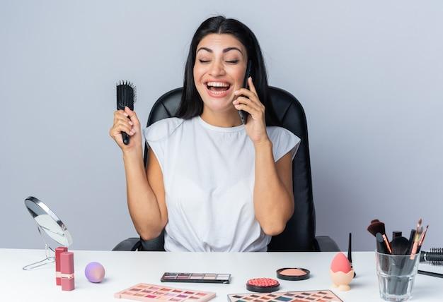 눈을 감고 웃고 있는 아름다운 여성은 화장 도구를 들고 테이블에 앉아 빗을 들고 전화 통화를 한다
