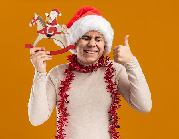 Laughing with closed eyes young guy wearing christmas hat with garland on neck holding christmas toy showing thumb up isolated on yellow wall