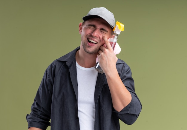 Laughing with closed eyes young handsome cleaning guy wearing t-shirt and cap holding rag with spray bottle around face isolated on olive green wall