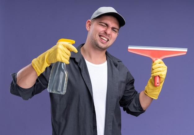 目を閉じて笑う若いハンサムな掃除人は、紫色の壁に隔離されたモップの頭とスプレーボトルを保持しているキャップと手袋のtシャツを着ています