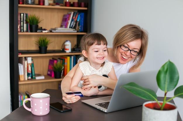 Смеющаяся женщина и ее маленькая дочь смотрят на ноутбук и делают покупки в интернете