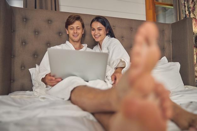 침실에서 노트북을 즐기면서 웃는 여자와 남자