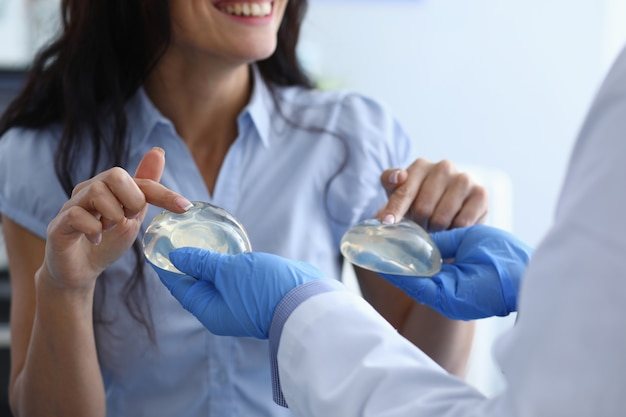 Laughing woman chooses breast implants from doctor