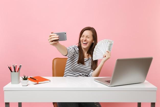 Смеющаяся женщина делает селфи на мобильном телефоне, держа пачку долларов, наличных денег во время работы за столом с ноутбуком