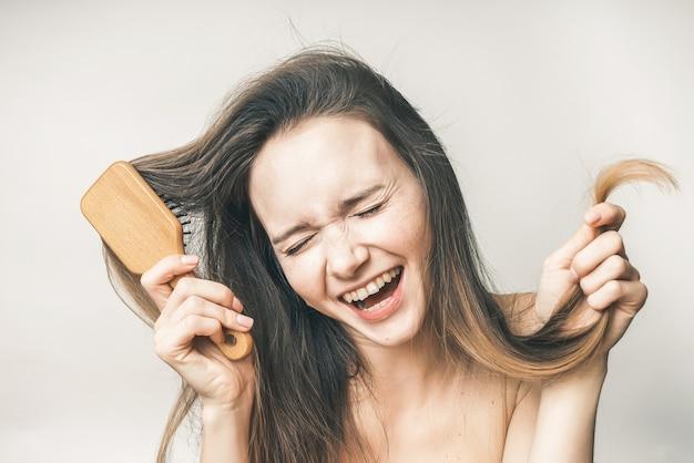 웃는 여자는 아름다운 머리카락, 행복한 건강 관리를 즐긴다