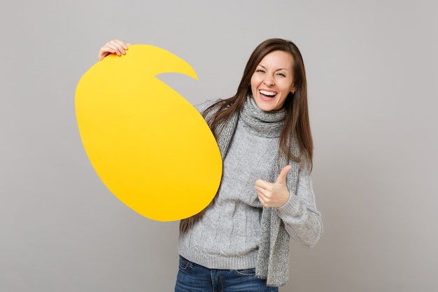 Laughing woman in gray sweater, scarf showing thumb up, hold yellow empty blank say cloud, speech bubble isolated on grey background. healthy fashion lifestyle, people emotions, cold season concept.