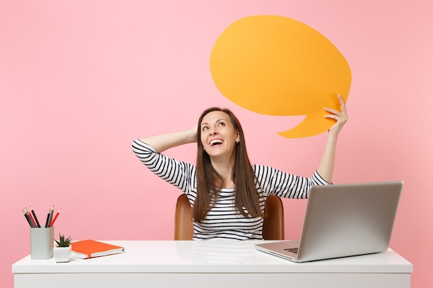 Laughing woman hold yellow empty blank say cloud speech bubble work at white desk with pc laptop isolated on pastel pink background. achievement business career concept. copy space for advertisement.