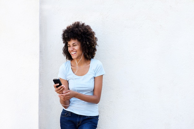 Laughing woman holding mobile phone standing by white wall