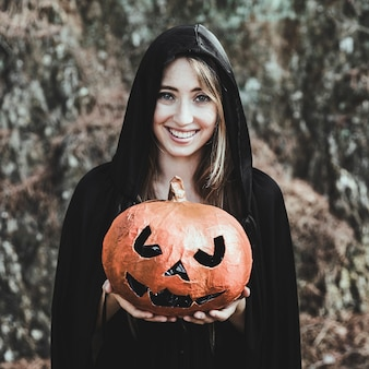 Laughing woman holding pumpkin in park