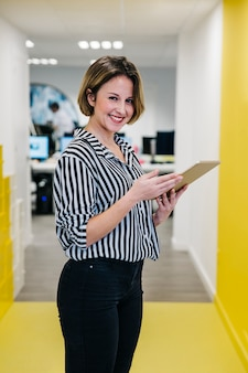 Laughing woman holding tablet in office