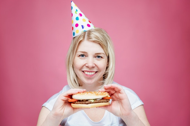 Laughing woman in home clothes and a festive cap is holding a hamburger. lonely birthday in isolation period on the background of coronavirus. pink background.