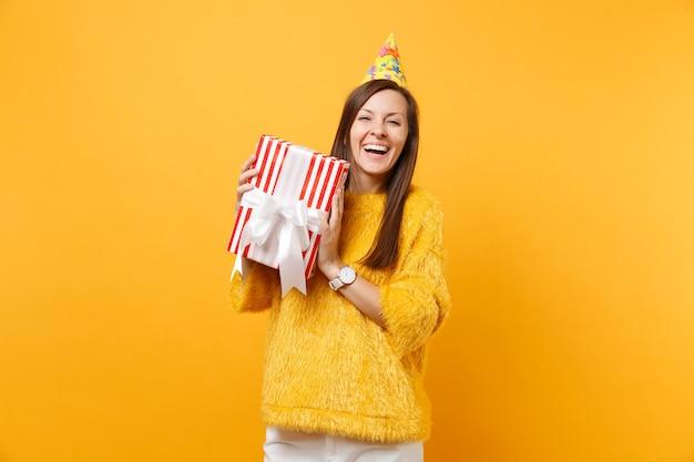 明るい黄色の背景で隔離の休日を楽しんで、祝うギフトプレゼントと赤い箱を保持している誕生日パーティーハットで笑う女性。人々の誠実な感情、ライフスタイルのコンセプト。広告エリア。