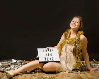 Laughing woman in evening wear with tablet on floor